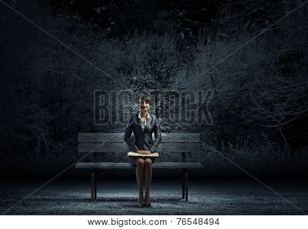 Young smiling businesswoman sitting on bench with book in hands