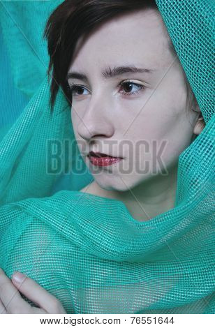 portrait photo of beauty pale model girl wrapped in green fabric close up in studio with studio ligh