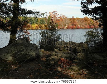Fire pit by the water lined with fall trees