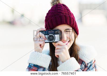 Teenage girl using vintage camera