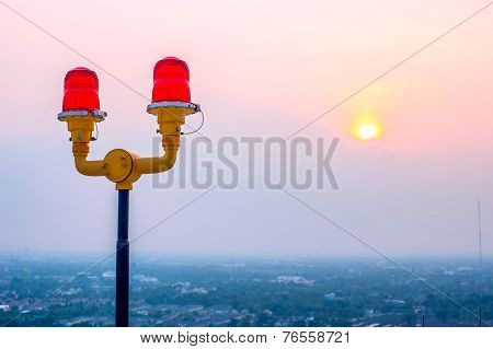 Dual red light on top of building against dawn sun light