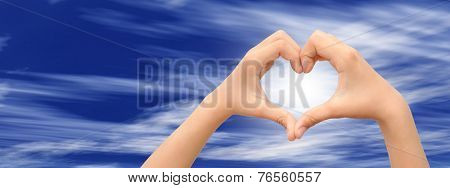 Concept or conceptual human male or man and woman hands in love, Valentines shape or symbol of heart over blue sky banner background
