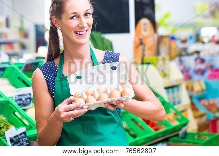 Female organic Supermarket clerk filling up egg storage racks in fresh department