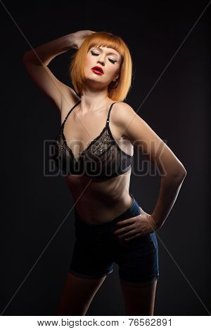 Languorous red-haired woman posing at camera