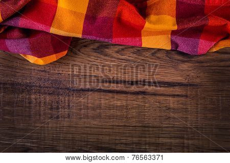 Top view of checkered napkin on empty wooden table