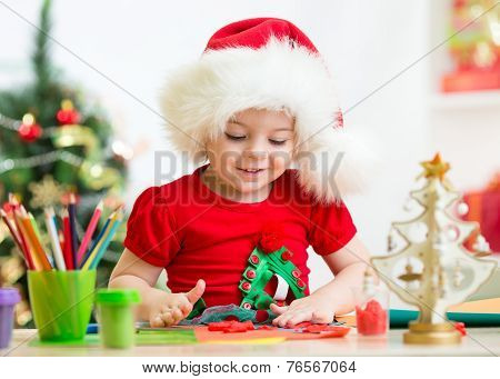 kid in Santa hat making Christmas decorations from plasticine