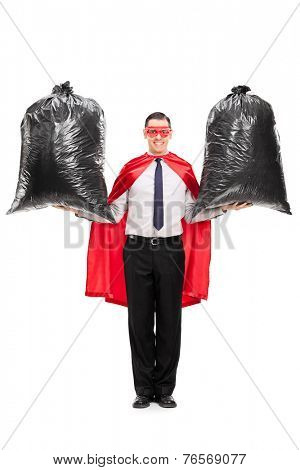 Full length portrait of a young superhero holding two trash bags isolated on white background
