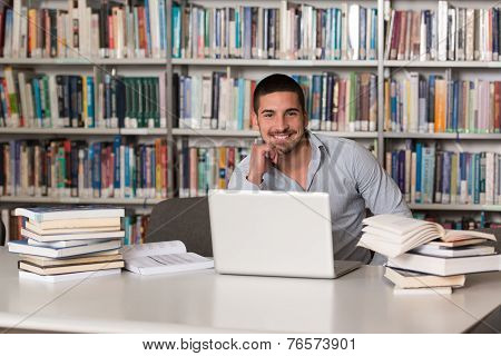 Young Student Using His Laptop In A Library