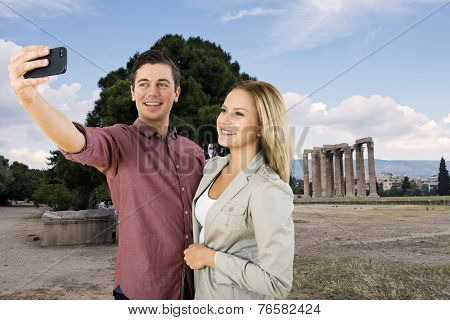 Young couple on vacation taking a selfie in ront of the ruins of an ancient Roman Temple