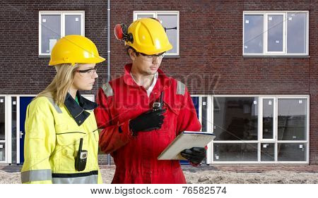 Foreman and real estate development manager going over an electronic checklist during the delivery and completion of a new housing development, constructed from prefab elements