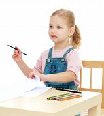 stock photo of montessori school  - Little girl draws pencils sitting at the table - JPG
