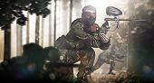 stock photo of paintball  - Paintball team in action rainy forest location - JPG