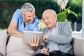stock photo of nursing  - Male nurse and senior man smiling while using tablet computer at nursing home porch - JPG