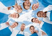 stock photo of huddle  - Directly below shot of diverse professional cleaners standing in huddle against sky - JPG