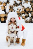 pic of laika  - Cute girl hugging her friend the dog Laika on the background of the forest in the winter - JPG