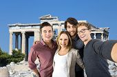 stock photo of hopper  - Four tourists taking a selfie in front of an old Greek temple during their vacation - JPG