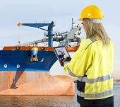 stock photo of dredge  - Female quality assurance manager takinga picture of a dredging vessel with her tablet - JPG