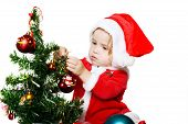 image of new years baby  - sweet baby Santa girl decorating a new year tree - JPG