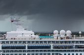 image of cruise ship caribbean  - A luxury cruise ship with storm clouds in background - JPG