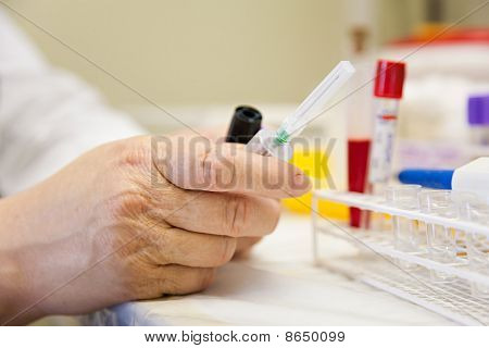 Female Nurse Preparing Equipment For Taking Blood In Shallow Depth Of Field