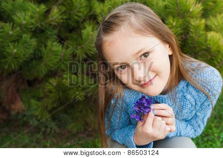 Close up portrait of a cute little girl, holding small bouquet of violets, wearing blue pullover
