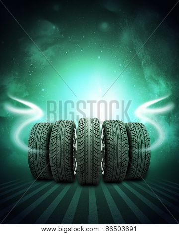 Wedge of new car wheels. Background is night sky and stripes at bottom