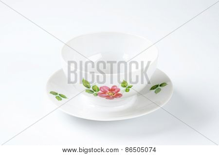 white tea cup with floral decor on white background