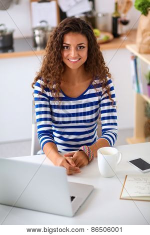 Smiling young woman with coffee cup and laptop in the kitchen at home