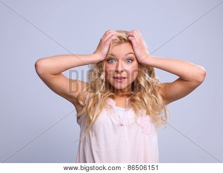 Young emotional woman, standing on grary background