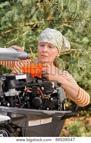 Senior Woman Pouring Oil Into Engine