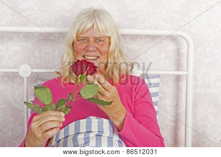 Smiling Woman In Bed With Rose