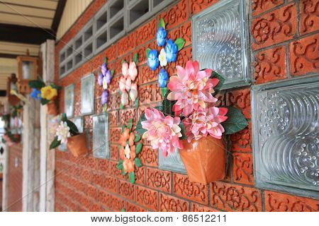 Artificial Flowers Decorate On Brick Wall
