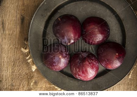Fresh Plums In Natural Light Setting With Moody Vintage Retro Style