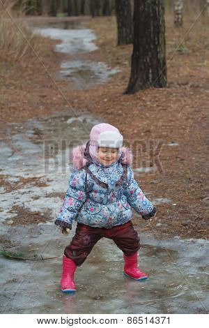 Two Years Old Toddler Girl Playing In Icy Puddle