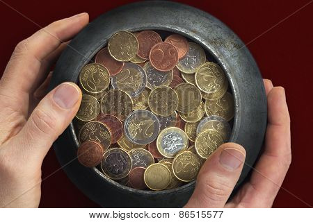 Man's Hands Holding A Pot With Euro Coins