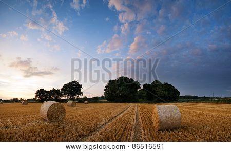 Stunning Summer Sunset Landscape Over Feild Of Hay Bales