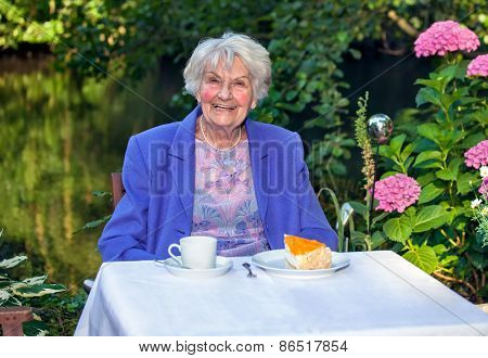 Happy Senior Woman Having Snacks At The Garden