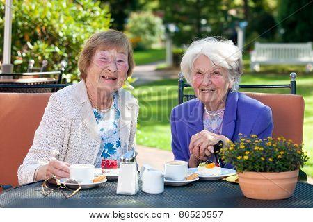 Two Happy Senior Ladies Having Snacks Outside