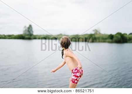 Little girl throwing stones in water at the beach