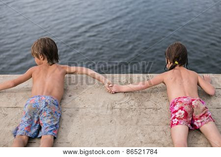 Fraternal twins tanning on wooden deck at the lake