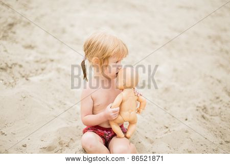 Toddler girl with red hair at the beach kissing her baby doll