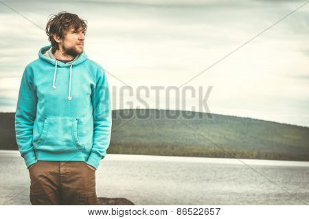 Young Man standing alone outdoor with scandinavian mountains and lake on background
