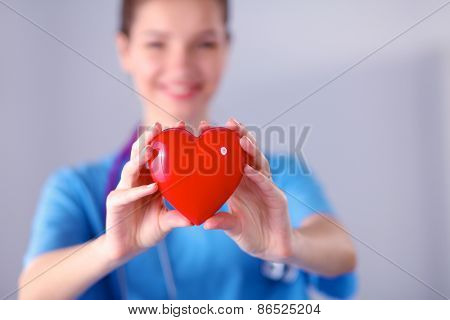 Young woman doctor holding a red heart, standing on gray