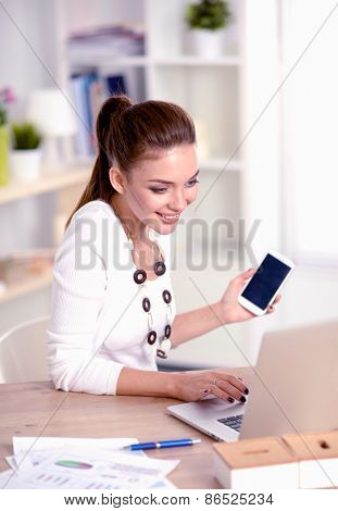 Young businesswoman sitting and talking on phone .