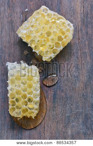 Honeycomb and honey drops over old wooden table