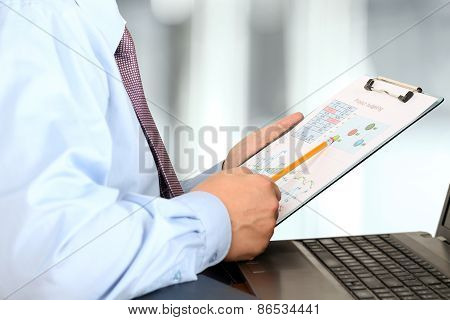 Businessman Sitting In Front Of Laptop,  Analyzing  Data In  Graphs