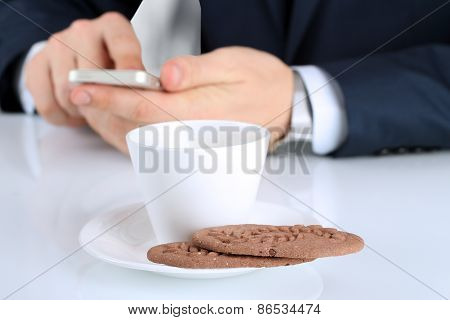 Closeup Image Of Cup Of Coffee With Cookies .businessman Holding  And Using The  Mobile  Smart  Phon