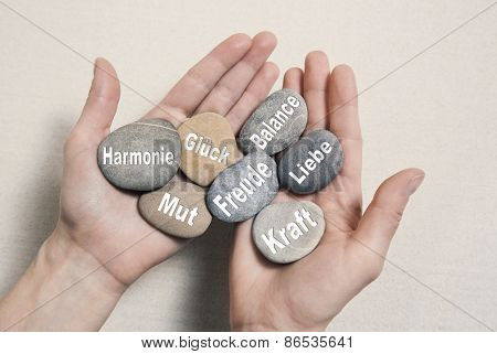 Inner balance concept with hands holding stones in german language: harmony, courage, luck, happiness, power and love.