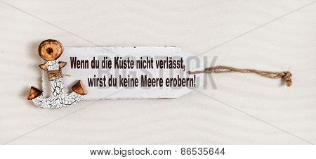 German slogan on a wooden sign with anchor with the text: if you don't leave coasts you can not discover the oceans. Concept for courage.