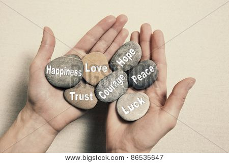 Inner balance concept: hands holding stones with the words happiness, love, trust, courage, hope, peace and luck.